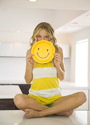 Young Woman Holding Smiley Face